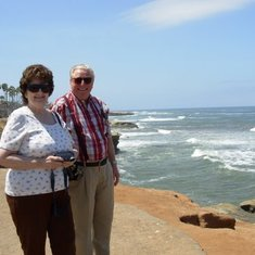 Anita & Jim standing by the Pacific Ocean in San Diego CA