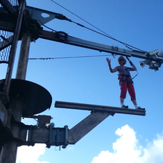My wife on the ropes course walking the plank.